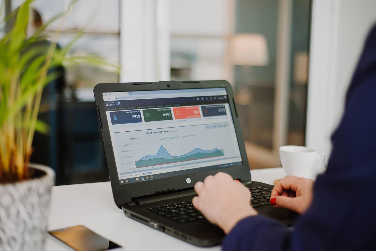 Usuário com um notebook sobre a mesa acessando o sistema SGCOR Gestão